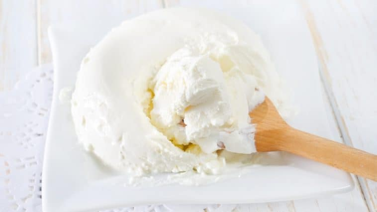 mascarpone being scooped with wooden spoon