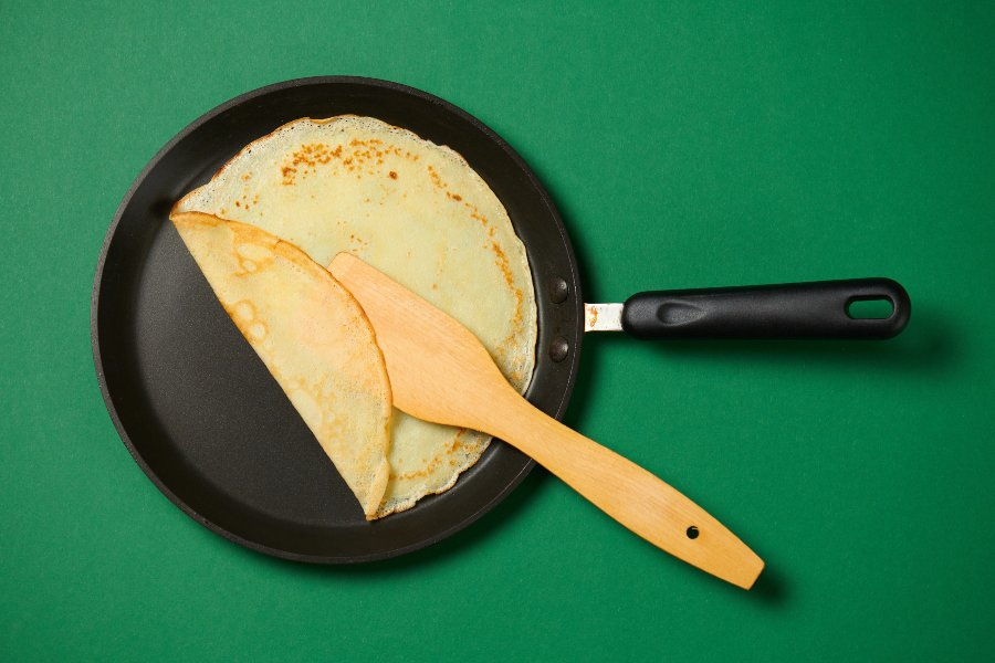 folded crepe in crepe pan and spatula