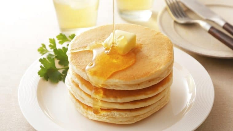 maple syrup poured over pancakes on plate