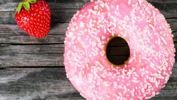 strawberry glazed donut next to a strawberry