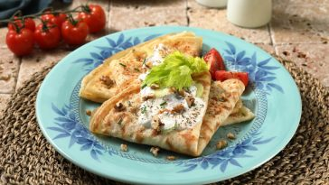 plate of stroganoff crepes with fresh tomatoes and steak
