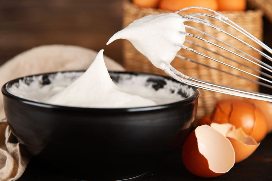whisk and bowl of meringue