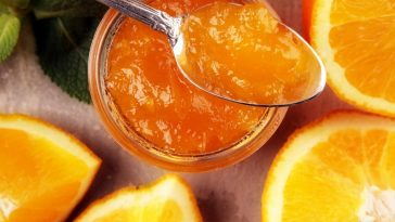 glass jar and spoon of orange marmalade