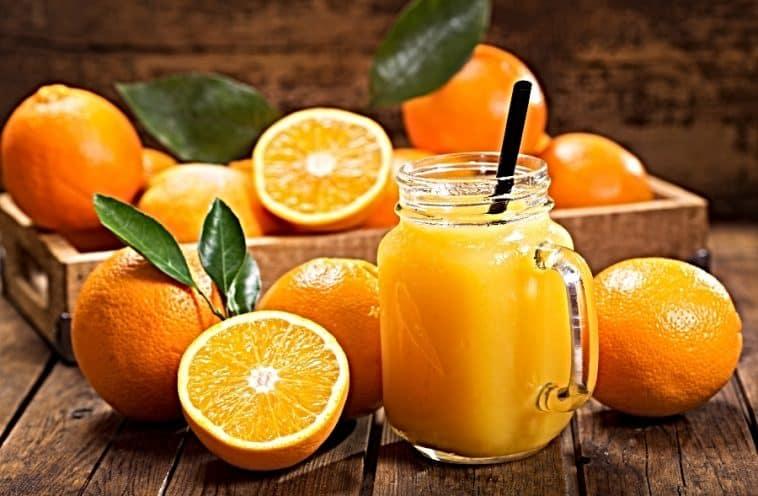 orange juice in a jar and fresh oranges