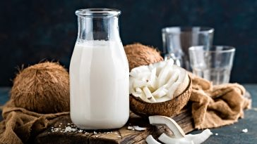 coconut milk in glass container and whole coconuts