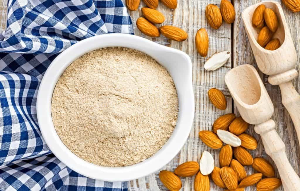 almond flour in bowl with scoop of almonds