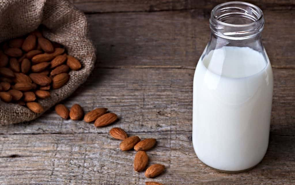 almond milk in jug and whole almonds