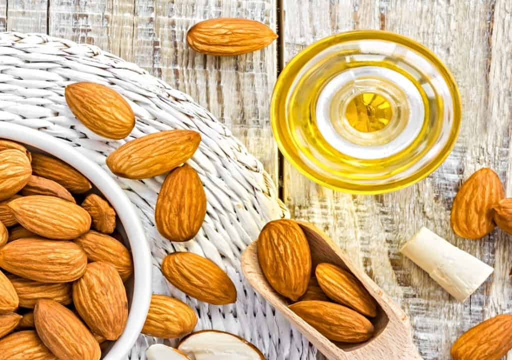 almonds and almond oil on table