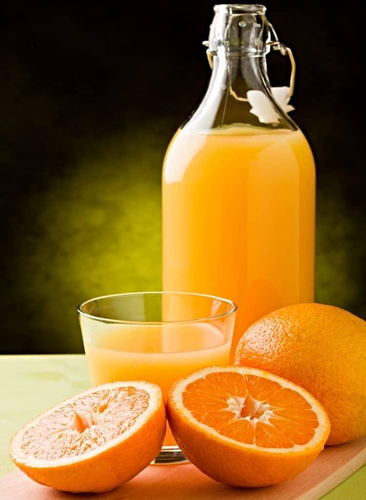 bottle and glass of orange juice and whole oranges