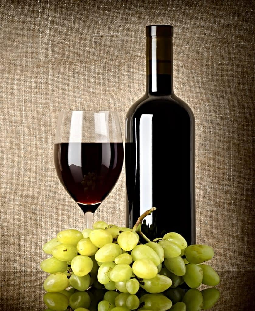 bottle and glass of red wine and grapes