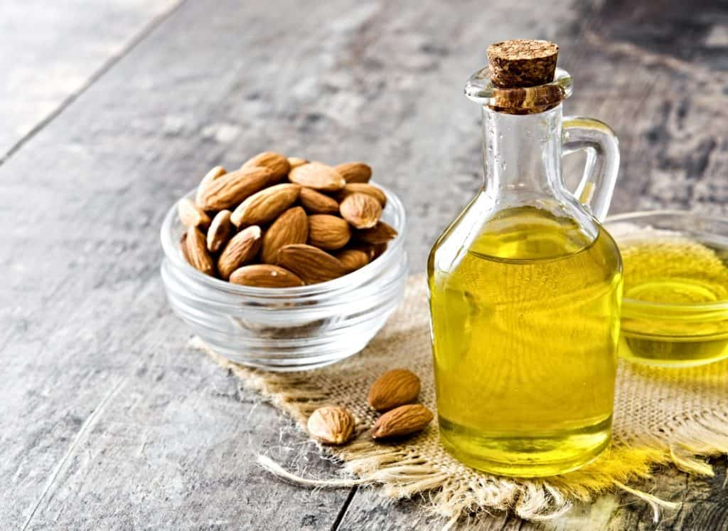 bottle of almond oil and bowl of whole almonds