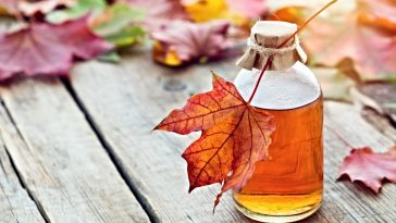 bottle of maple extract on table with maple leaves
