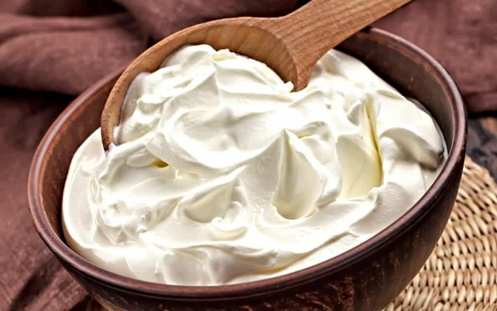 bowl of sour cream with wooden spoon