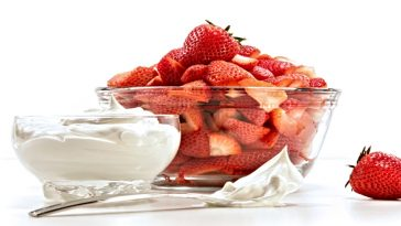 bowl of whipped cream and strawberries