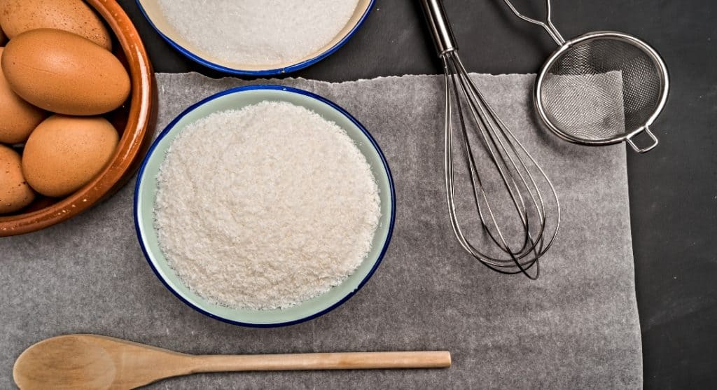 coconut flour in bowl and eggs and whisk
