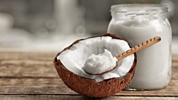 coconut oil in a glass jar and a half a coconut