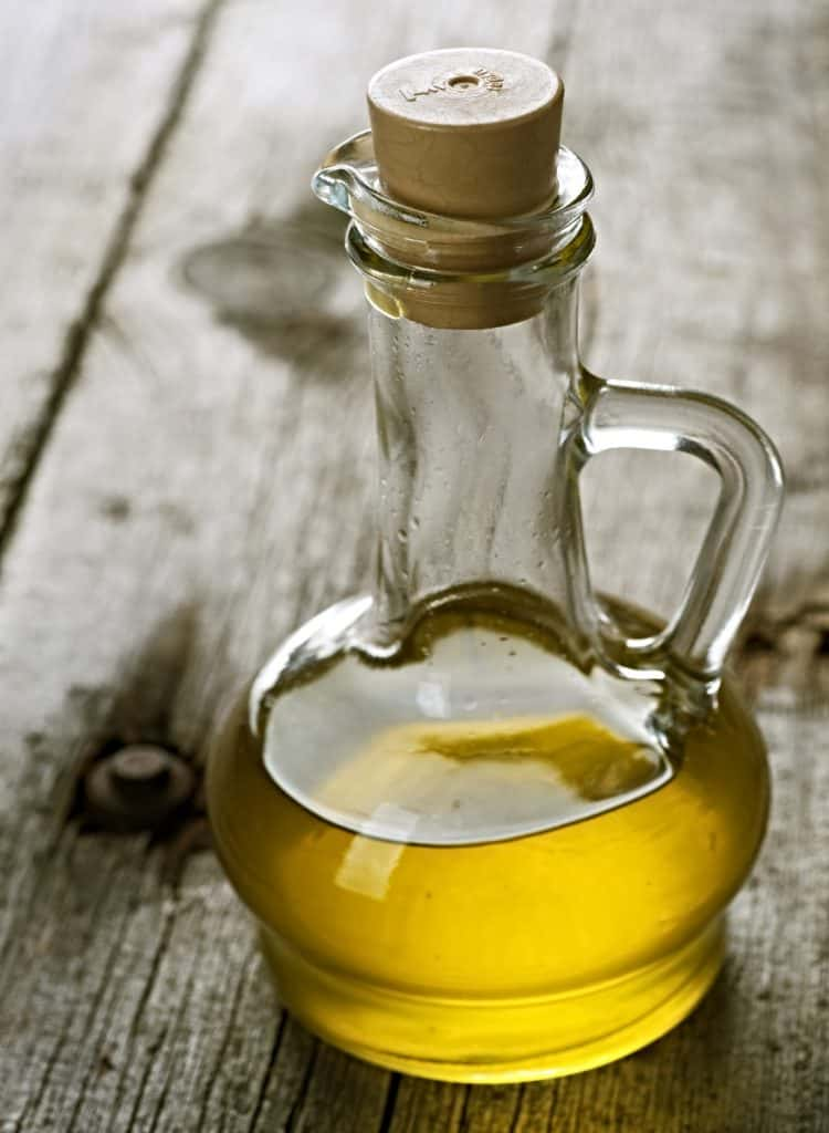 glass jar of olive oil on table