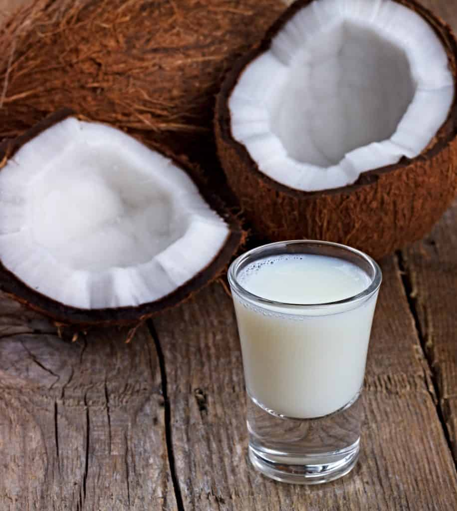 glass of coconut milk and whole coconuts