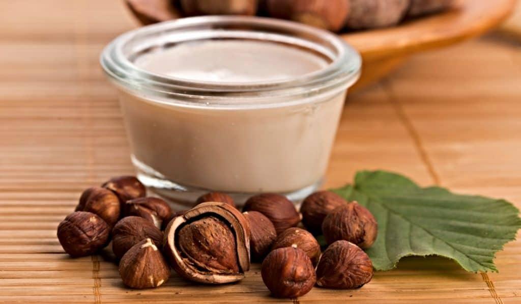 glass of hazelnut milk and hazelnuts