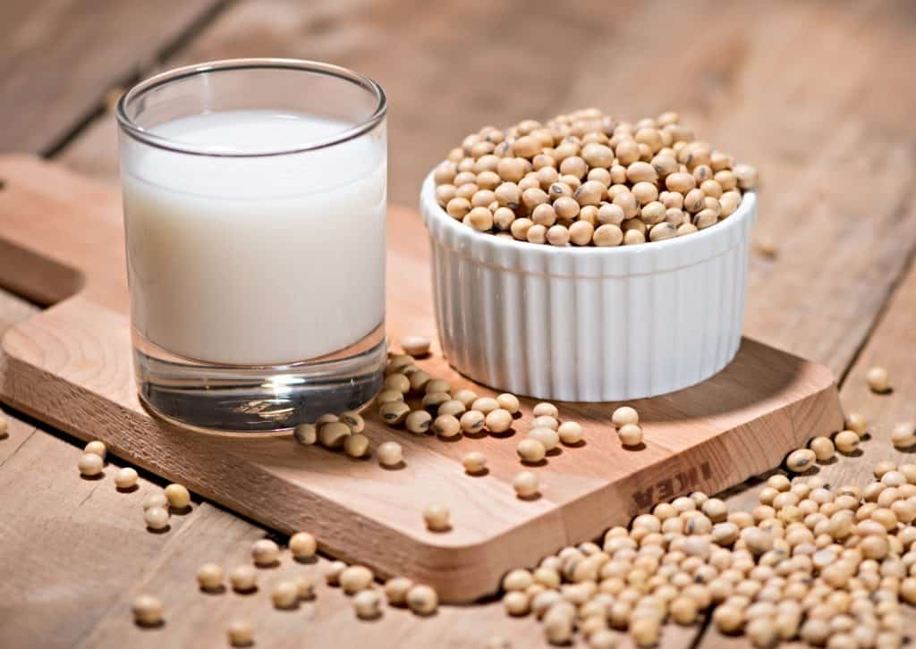 glass of soy milk and cup of soybeans