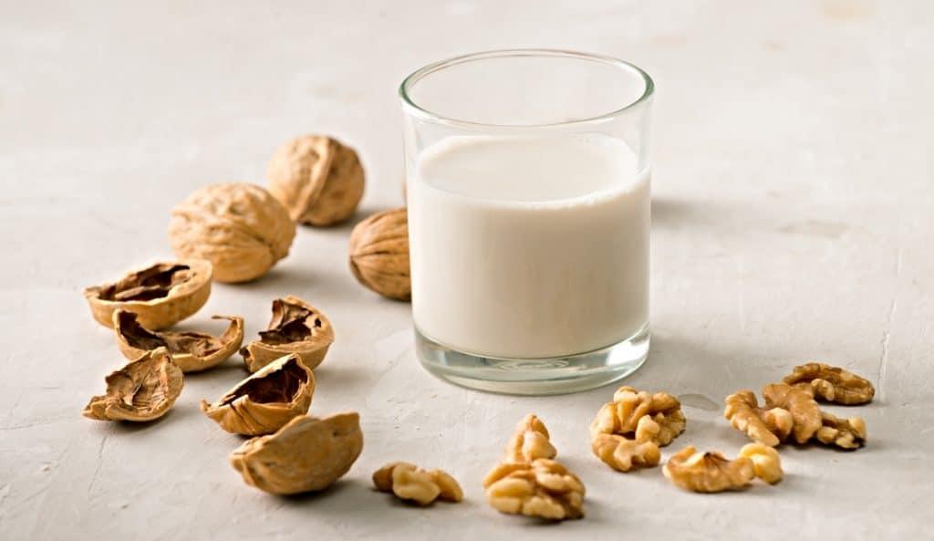 glass of walnut milk and walnuts