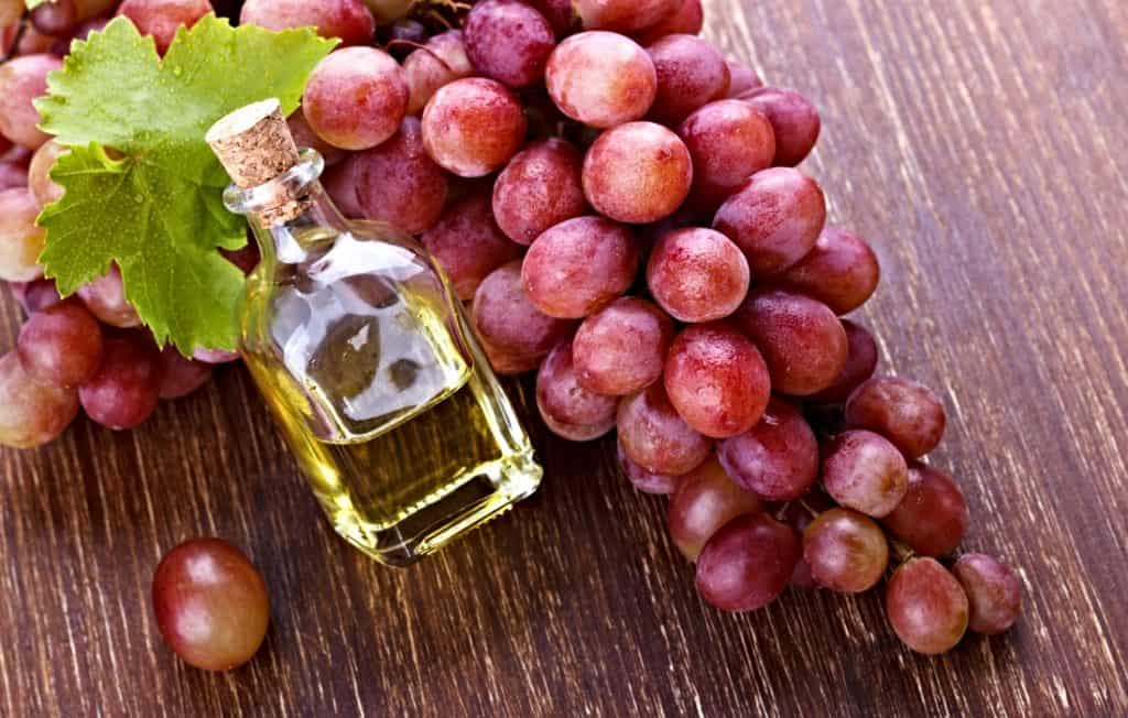 grapeseed oil in bottle and bunch of fresh grapes