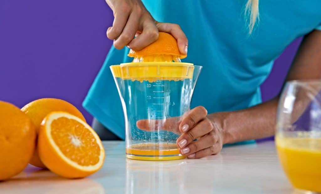 half an orange being juiced by woman
