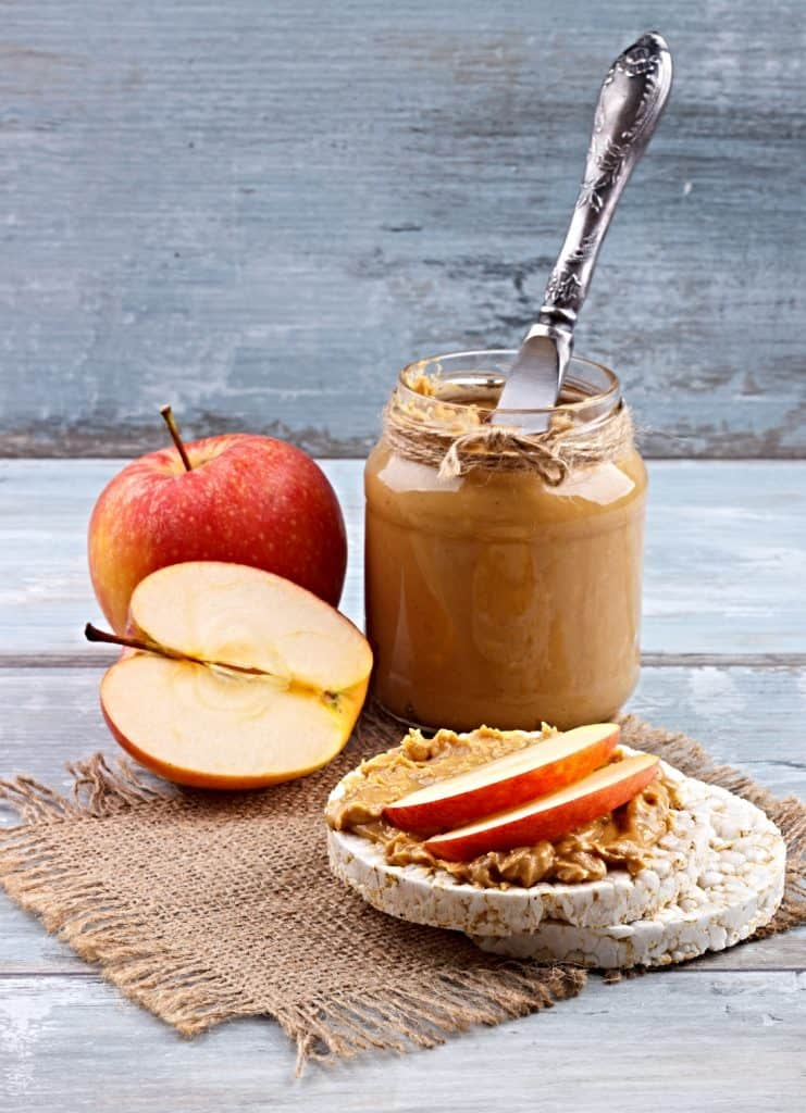 jar of creamy peanut butter with knife and apples