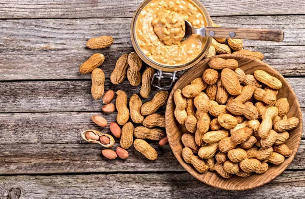 jar of crunchy peanut butter and shelled peanuts