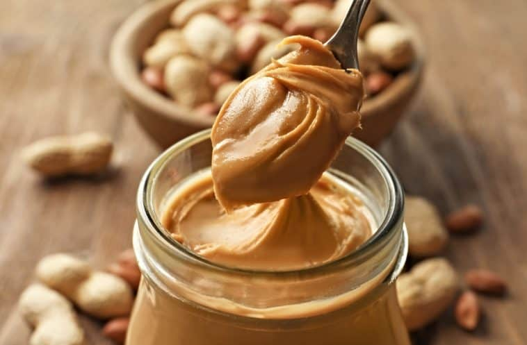 jar of peanut butter with spoonful of peanut butter