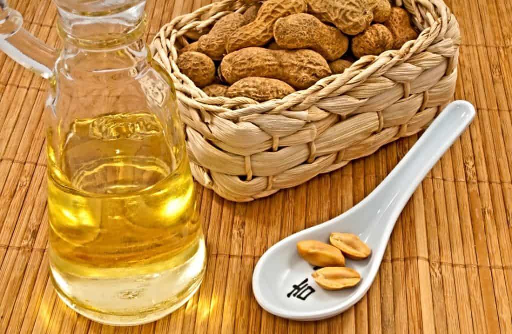 peanut oil in bottle with whole peanuts in basket