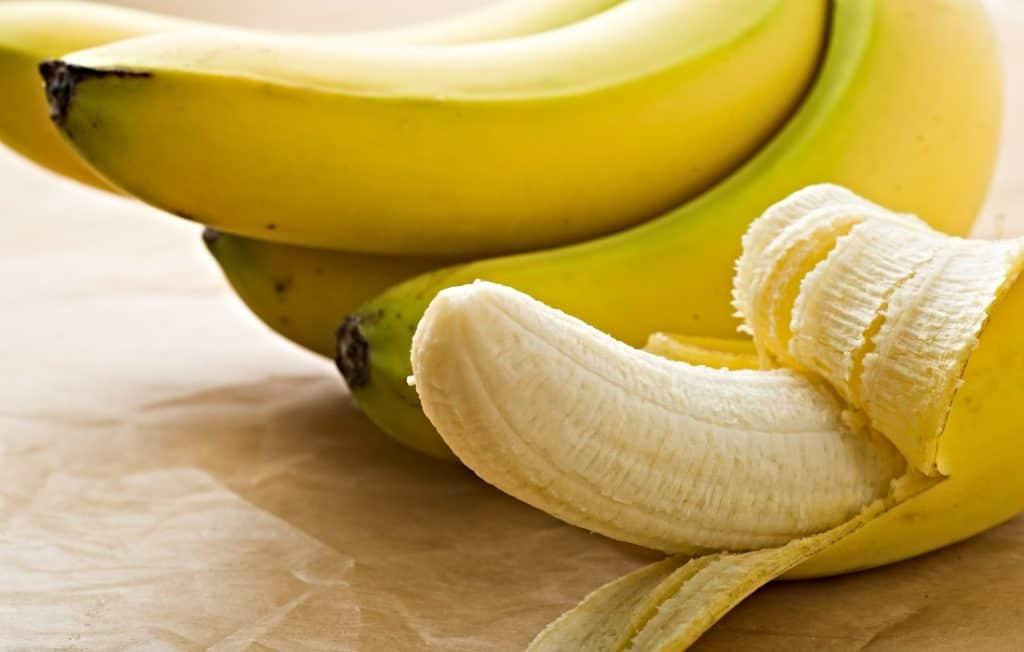 peeled banana and a bunch of bananas