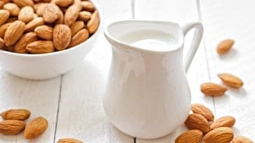 pitcher of almond milk and bowl of almonds
