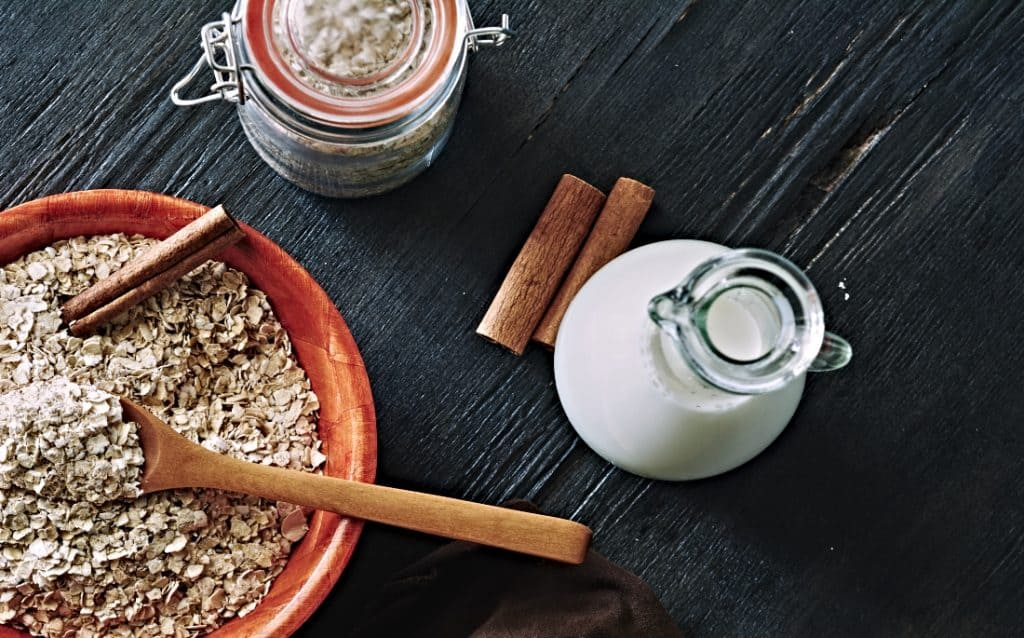 pitcher of oat milk and oats in a bowl