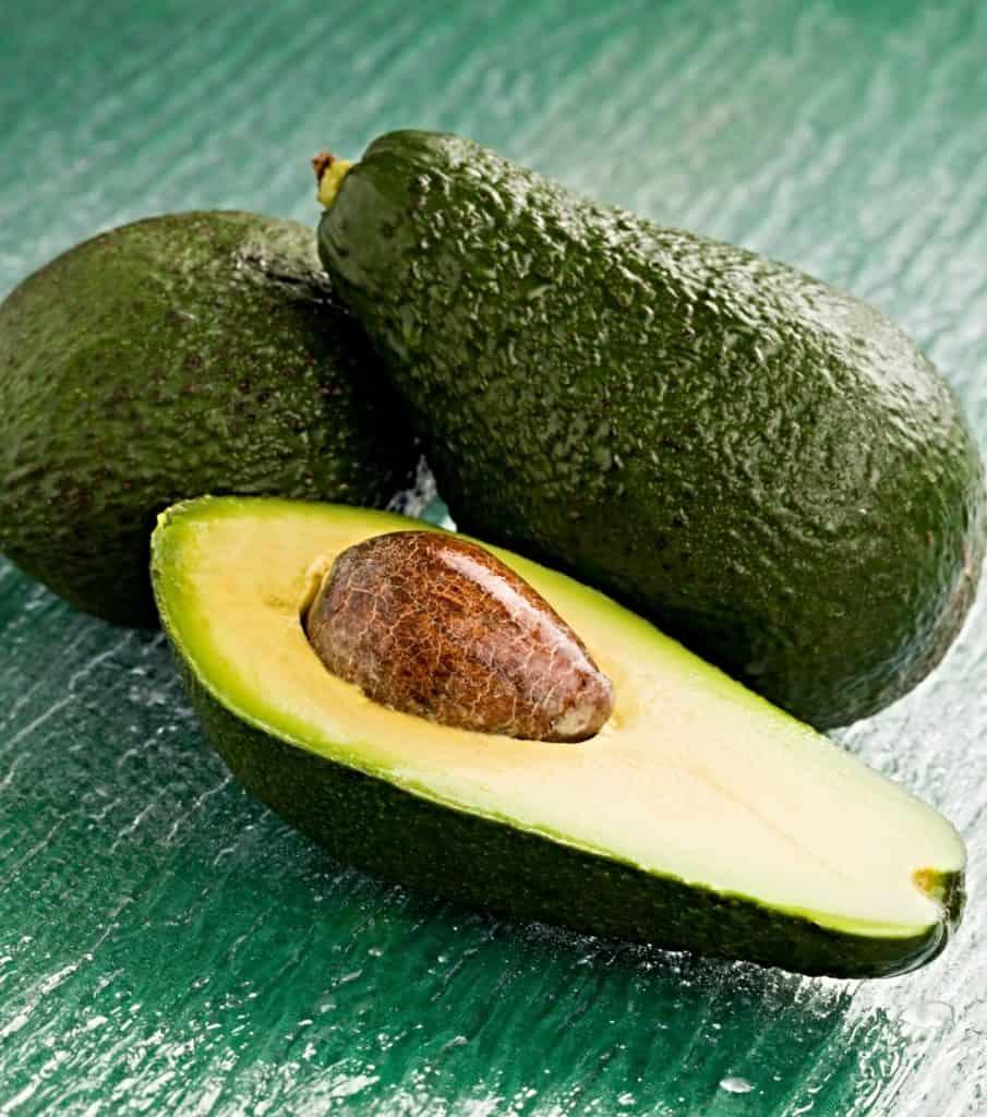 three avocados on table
