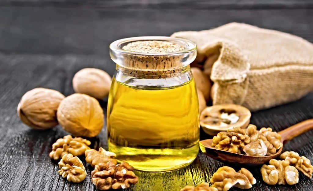 walnut oil in jar and whole walnuts in bag
