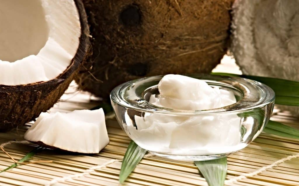 whole coconut and coconut oil in bowl