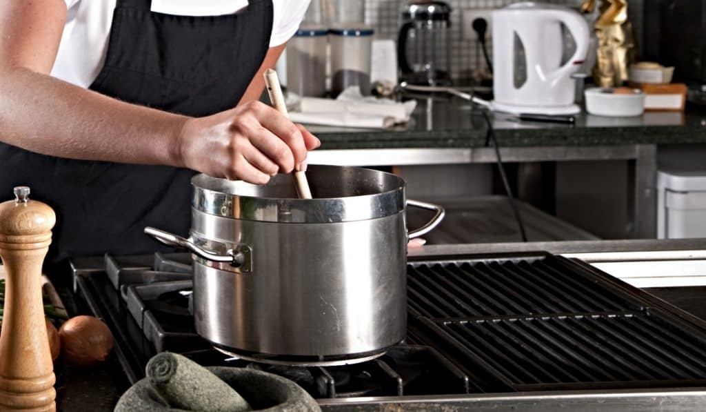 woman reducing fruit sauce in pot