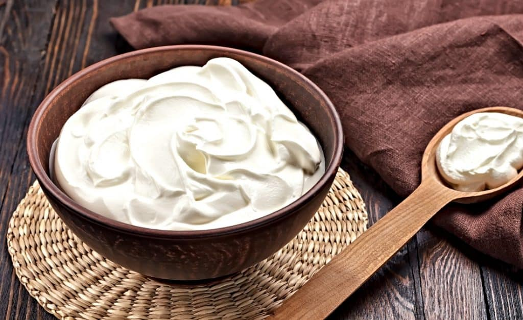 wooden bowl and spoon with sour cream