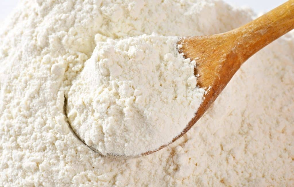 wooden spoon scooping all purpose flour