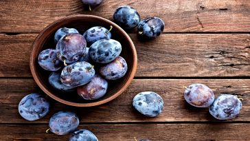 bowl of fresh plums on table