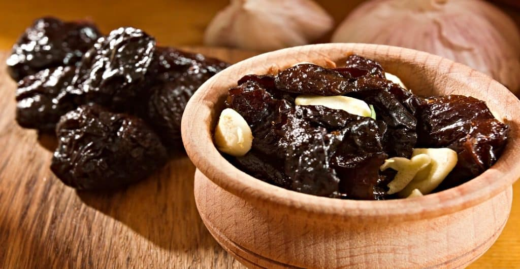 garlic and prunes in a bowl