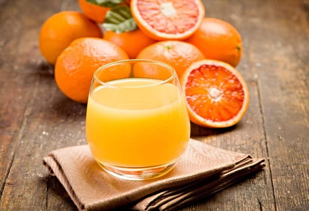 glass of orange juice and fresh oranges